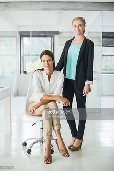 Two businesswomen in a open office looking into camera