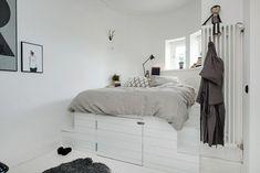 Чтобы спрятать больше вещей, кровать решили установить на подиум. В него отлично помещаются сезонные вещи и обувь. В спальне есть и небольшой гардероб. Здесь всё предельно просто: несколько широких открытых полок, штанга для вешалок, достаточное количество коробок для хранения. Кстати, не обошлось и без оригинальных решений. Частично вещи хранятся в деревянных ящиках. Это в очередной раз доказывает, что бюджетный интерьер может быть стильным и красивым.