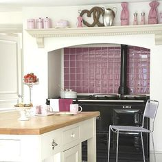 I love an Aga so much - providing I would never have to go outside I would love to live in a climate where I could have one.  I love this black one with the pink splashback - perfect.