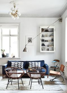 A cozy living room with white walls, industrial modern lighting, and leather chairs.