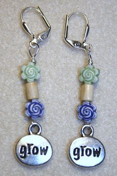 "Handcrafted by Teal Palmetto, LLC. Are you a gardener or do you know someone who is?  These wonderful earrings express the mantra of anyone who loves to make things grow!  Pewter silver-tone ""grow"" charms dangle from wood and flower beads.  This pair has silver leverback ear wires.  Price: $12."