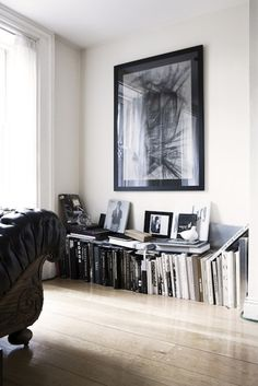 a sleek, black, low book case (preferably lighted) would look great under the picture to house the books....and a few on top displayed on lucite stands, with a few stacked to the side would look GREAT!