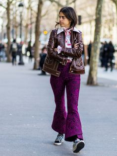 Leandra Medine wears a printed blouse, patent leather jacket, flared trousers, and Golden Goose sneakers