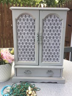 Reimagined and given new life!  Shabby Chic Jewelry Armoire is painted with chalk paint, distressed in all the right places and waxed for a perfect finish.  This lovely wooden armoire features two doors opening to reveal a large compartment with two roating necklace/bracelet hangers. Below is a roomy drawer for other precious valuables  Dimensions: 15 tall, 10 1/4 Wide, 6 1/2 Deep  This items distressing lends character and charm. It is a refinished vintage item. Please feel free to ask any…