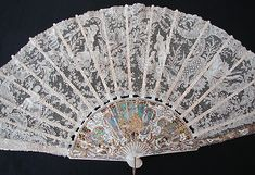 Magnificent Figural Brussels Point De Gaze Lace Fan  A stunning design on this Brussels Point De Gaze fan leaf. It is always quite rare to find figurals like this in lace! A wonderful ornate scene, a young boy hunting with dog, and a lady threshing wheat. There are two other figurals, a young boy with a bushel of wheat and another picking grapes. A beautiful pastoral scene that seems to be celeberating the harvest and the hunt.