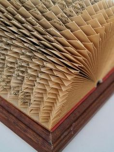 book folding patterns, vintage book with red covers, placed in wooden frame, opened to reveal intricate geometrical pattern, made from folded pages Folded Book Art, Paper Book, Paper Art, Paper Crafts, Old Book Crafts, Book Page Crafts, Book Folding Patterns Free, Christmas Photo, Recycled Books