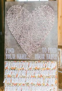 A huge DIY wooden board featuring a heart made of criss-crossed string and seating assignments pinned on floral fabric | Brides.com