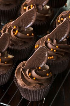Chocolate orange cupcakes topped with chocolate orange buttercream, a slice of Chocolate Orange and orange sprinkles on a cooling rack.