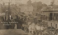 A photograph of a busy and crowded street full of carts and men working in front of the Prospect Hotel.