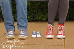 parents feet with baby shoes; pregnancy reveal; maternity shoot