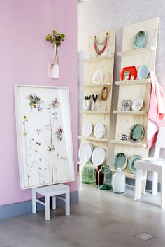 Like the idea of free standing board leaning against wall with shallow shelves. Would use tongue and groove boards for back.  Great way to keep art supplies visible and within easy reach