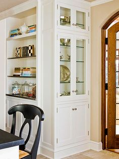 Now Showing The homeowners' silver collection takes center stage in a large bookcase-style display cabinet. Wrap around cabinetry