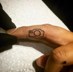 Tiny camera tattoo on finger by Savage Sal