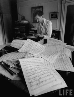 Composer Alan Hovhaness, working in score littered studio with black cat nestling amongst the papers on the piano.; Photograph byGordon Parks, December 1955.Source: LIFE Photo Archive, hosted by Google.