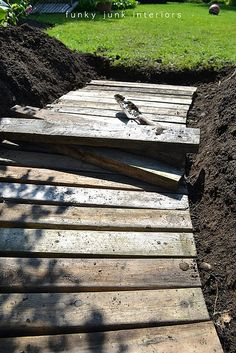 A pallet wood garden walkway pallet walkway, I like this but I really need something that will not be slippery. This walkway will have lots of traffic! Pallet Walkway, Wood Walkway, Garden Pallet, Wood Path, Walkway Ideas, Pallet Pathway Ideas, Wooden Pathway, Walkway Lights, Outdoor Projects
