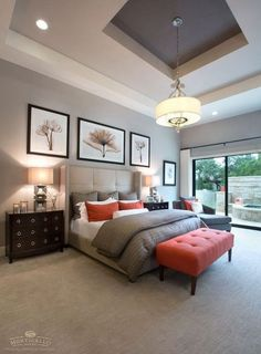 Gray master bedroom with bright brown touches in. Bright brown tufted bench and throw pillows add pop of color to this neutral bedroom.