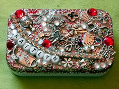 Money tin made from an Altoid min tin for a little girl. These tins close tightly and are perfect for this project! I used Mod Podge, glitter, rhinestones, beads,buttons and charms.