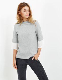 Die angesetzten Trompetenärmel aus plissiertem Chiffon geben dem cleanen Sweater ein modisches Update.