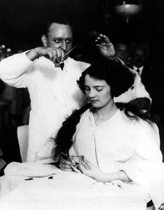 A young lady getting her hair bobbed in a men's barber shop, ca. 1920s
