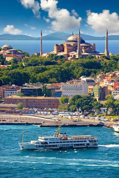 The exterior of the 6th century Byzantine (Eastern Roman) Hagia Sophia ( Ayasofya ) on Sarayburnu or Seraglio Point with a ferry and the banks of the Golden Horn in the foreground, Istanbul Turkey.