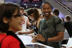 THE ORIGINALS star Charles Michael Davis shares a laugh with a fan at the Warner Bros. booth at Comic-Con 2014. #WBSDCC