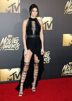APRIL 2016: Kendall Jenner walked the red carpet at the 2016 MTV Movie Awards in a black Kristian Aadnevik dress with a high-low hemline and DSquared2 gladiator heels. Photo: Tinseltown / Shutterstock.com