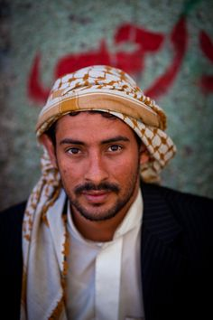 Portrait of a young Yemeni with the Keffiyeh in the old city Sana'a, Yemen.  The keffiyeh is a traditional Arab headdress fashioned from a square, usually cotton, scarf. It is worn by Arab men.  It is found in arid regions to provide protection from sun exposure, as well as to protect the mouth and eyes from blown dust and sand. Its woven check pattern may have originated in ancient Mesopotamian representation of fishing nets or ears of grain. (V)