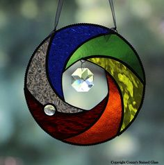 Different textured rainbow colored glass give this suncatcher an elegant look. I added a glass nugget to give it an appealing look. Dangling from the center is a 1.25 octagon crystal. I framed this suncatcher with chain. This suncatcher measures 6 in diameter. I hand cut and grind every glass piece and use the Tiffany Foil method to construct these suncatchers. Hooks are soldered for hanging. I will even include the ribbon as shown for hanging.