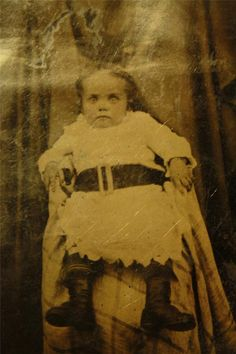 Post mortem? I doubt it. Yes, the child sits in a chair. Yes, it looks as if she's strapped with a belt to hold her up. But the hands are clamping on the chair and the look in her eyes is lively. It seems more that she's frightened to death for the photographer or the whole event!