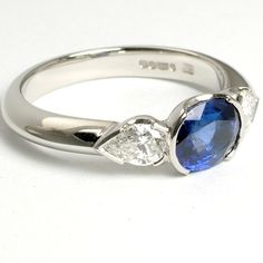 This bespoke engagement ring was uniquely designed and handmade in platinum. It features a stunning oval sapphire with matching pear diamonds in a modern trilogy reveal setting