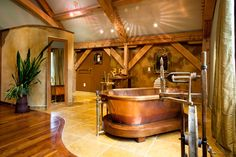 Bathroom with copper bathtub and sink in timber framed interior. Sophisticated, Medieval inspired design.