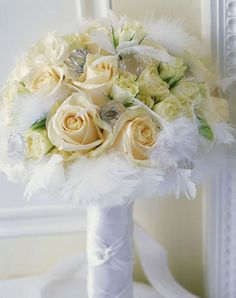 Bridal bouquet of satiny white roses, glittering crystals and soft white feathers.