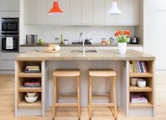 This neat breakfast bar has tucked-under stools, integrated power points so you can plug in any kitchen appliances you need, and even sports matching-wood alcove shelving for displaying pottery and books.