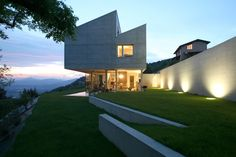 Geometric top-heavy concrete home built on edge of steep slope