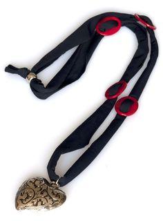 Bella come la dea Dafne, questa collana è ricca di materiali: stoffa, madreperla e argentone. Un grande cuore traforato in argentone trionfa al centro della collana con inserti di madreperla rossa.