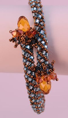 "GJ Shop Clinging Vine Bracelet Kit ©2009 as seen in Beadwork Magazine April/May 2012 Tubular Netting, Any Skill Level Swarovski briolettes & bicones, 15° and 1.5 mm cube beads, plastic tubing, oval memory wire in your choice of: 2.2 x 2.7"" (medium) for an average size wrist, or"