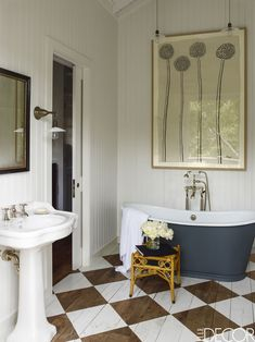 The master bath tub is by Waterworks, the sink and all the fittings are by Lefroy Brooks, and the painting is by Hugo Guinness; the walls are painted in Benjamin Moore's White Dove, the floor in Farrow & Ball's All White.