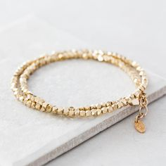 Sparkling gold plated double faceted wrap bracelet. Geometric silver nuggets plated in gold coil twice around your wrist in this simple, modern double wrap