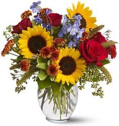Autumn Skies  Give someone the colors of sunshine and blue skies… send this cheerful mix of bright yellow sunflowers and pale blue delphinium blossoms, accented with velvety red roses and a bit of feathery millet. It's like a bouquet full of happiness!