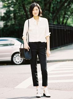 Button-down shirt tucked into black trousers and white ankle boots