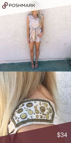 """White Gold Dressy Romper This gorgeous romper checks all the boxes. It has Egyptian-looking embellishment on each shoulder. It had a modified cowl neck, an elastic waist with four 2"""" tabbed belt loops, a slippery fabric belt, pockets, and a cuffed short hemline. Comfortable and sexy on. Bust: 38"""", Length: 34"""". 100% Polyester. H&M Pants Jumpsuits & Rompers"""