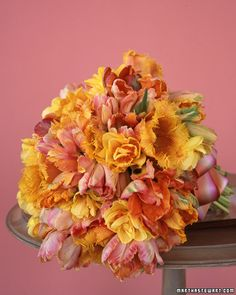 Exotic parrot tulips combine with fringed and viridflora tulips and double-petaled narcissus in a poetic bouquet, tied with a hand-dyed silk ribbon in complementary pastel shades. To keep the large array from flopping, stems were cut short. Since tulips are a thirsty flower, the bouquet should be kept in water until right before the ceremony.