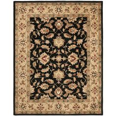 An intricate Oriental design and dense, thick pile highlight this handmade rug. This floor rug has a black background and a gold border and displays stunning panel colors of green, blue, red, ivory, pink and beige.