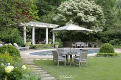 This Kingsley Bate aged teak table and chairs sits in between the perennial border and pool. It's a perfect lunch spot! A Planters design. Atlanta, GA.