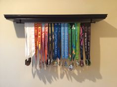 "To display all of our half marathon finisher medals we modified a 52"" floating shelf from Home Depot. To modify we added a curtain rod (purchased from Target for $5) by screwing it into the bottom of the shelf and reinforcing with Gorilla Glue. We installed the shelf on the wall as per the instructions provided and then strung our medals on the rod."