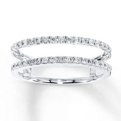 This elegant enhancer ring features a row of fiery round diamonds above and below your solitaire ring (sold separately). Fashioned in 14K white gold, the ring has a total diamond weight of 1/4 carat. Diamond Total Carat Weight may range from .23 - .28 carats.
