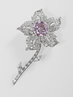 The Williamson pink diamond is a flawless stone discovered at the Williamson Diamond mine in 1947. The owner of the mine gave the uncut stone to Princess Elizabeth & Prince Philip upon their wedding.  The 54.5 carat rough diamond was cut in 1948; Cartier was commissioned to create a setting for the main 23.6 carat round brilliant cut pink diamond. It became the centre of a flower brooch with five white diamond petals, marquise diamonds for leaves & white baguette cut diamonds for the stalk.
