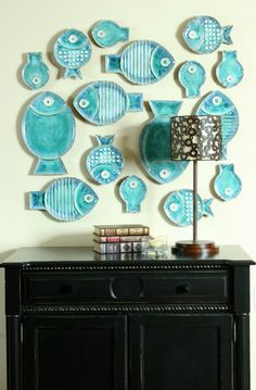 Collection of turquoise, modern fish dishes (by one maker) displayed in eclectic hallway. (Design/photo by Chelle Design Group via Houzz.)