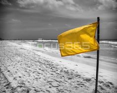 The yellow flag allowing the surf on a windy beach in Mexico