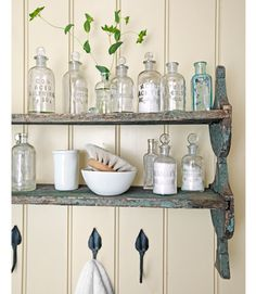STYLING / SHELVING :: On Display -- A weathered shelving unit, unearthed at a flea market, holds an assortment of glass-stoppered chemist's bottles. The wall is painted DKC-47 by Donald Kaufman. :: READ MORE: Rustic Lake House Decorating Ideas -- Cabin Decor Ideas @ Country Living | #countryliving